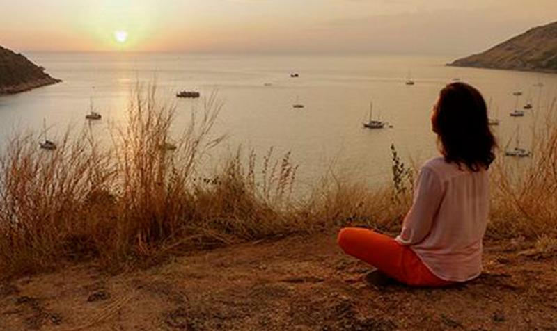 Kvinde sidder og kigger ud over vandet fra en skrænt
