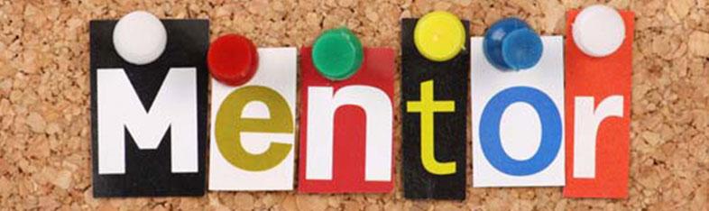 Bogstaver, der danner ordet mentor hænger på en opslagstavle med knappenåle