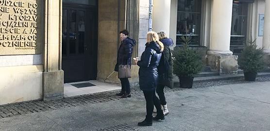 Tre mennesker fra projektet foran bygning