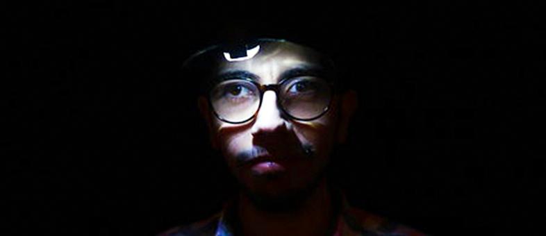 Dreng i teater i mørke - hans ansigt lyser op i mørket