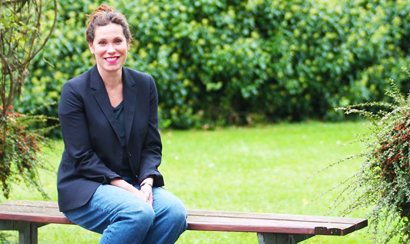 Marie Fasmer sidder på en bænk i IBOS have