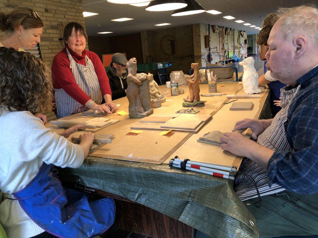 Helt bord med projektdeltagere former ler