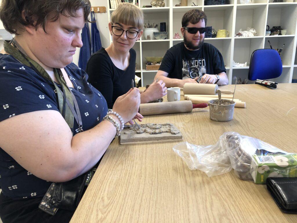 Tre projekt deltagere former ler