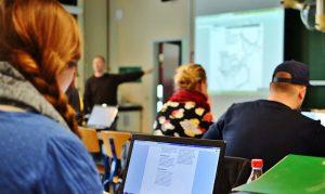 Foto af en underviser med powerpoint og mennesker, der lytter